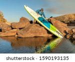 senior male paddler is launching an inflatable stand up paddleboard from a rocky shore of mountain lake - Horsetooth Reservoir in northern Colorado