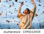 Man Throwing Autumn Leaves In...