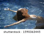 Small photo of Young woman swimming on back in swimming pool, differential focus