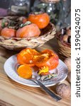 Small photo of An open persimmon on a saucer with a spoonful (eaten in the Italian manner). In the background wicker baskets with other persimmons and glass jars with aromas.