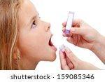 Young girl taking granules of homeopathic medication - closeup - stock photo