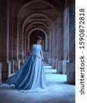 Small photo of Sad Snow Queen walks in old castle. blue silk long raincoat train flying motion. Elven hairstyle cute face. Vintage fantasy art retro style. Frozen Fabulous woman photo shoot. sun magic shine rays