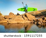 male paddler with an inflatable stand up paddleboard on a rocky shore of mountain lake - Horsetooth Reservoir in northern Colorado