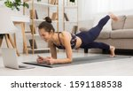 Small photo of Fit woman doing yoga plank and watching online tutorials on laptop, training in living room