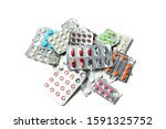 Small photo of A pile of pills in blister packs. Blister packs full of multi-colored pills isolated on a white background. Lot of tablets.