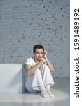 Small photo of Human emotions. Young man dressed in white sitting on the floor and feels a sense of fear