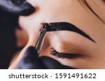 Small photo of beautician- makeup artist applies paint henna on previously plucked, design, trimmed eyebrows in a beauty salon in the session correction. Professional care for face.
