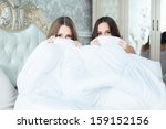 two girls in a bed hiding half... | Shutterstock . vector #159152156