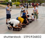 Small photo of NANSHAN CULTURAL PARK, HAINAN, CHINA - 5 MAR 2019 – Asian Chinese Buddhist devotees kneel and kowtow / bow in prayer to the Goddess of Mercy, Guanyin at Nanshan Temple