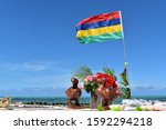 Small photo of Picture of a wooden statue representing the symbol of Mauritius the Dodo bird. Mauritius flag in background.