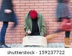 Homeless Man Sitting On A...