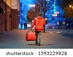 Small photo of Young deliveryboy walking with red thermal bag on night city street. Man of delivery service in hurry to deliver an order. Delivery service goes to give the order quickly to the client at night