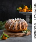 Small photo of Winter and christmas dessert, cranberry bundt cake with orange zest and fresh berries decorated with rosemary, tangerines and sugar powder on wooden plate (tray). Dark background.