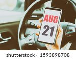 august 21st. Day 20 of month,Calendar date. Month and day placed on a smartphone screen in womans hand in car interior. artistic coloring.  summer month, day of the year concept