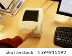 Woman finger on button on the pos printer on the office desk with computer and printed material