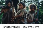 Small photo of Female Leader and Two Primeval Cavemen Warriors Threat Enemy with Stone Tipped Spear, Scream, Defending Their Cave and Territory in the Prehistoric Times. Neanderthals / Homo Sapiens Tribe