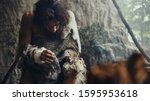 Small photo of Close-up Shot of a Primeval Caveman Wearing Animal Skin Hits Rock with Sharp Stone, Makes First Primitive Tool for Hunting Animal Prey. Neanderthal Using Flint Rock. Dawn of Human Civilization.