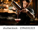 Bartender With Goatee Pouring...
