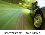 Side view of black sedan driving in forest. - stock photo
