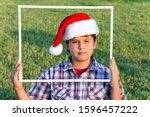 Small photo of Smart and handsome boy in a clownish cap of Santa Claus is looking through a white frame. Background is a green lawn. Concept portrait and advertising photo