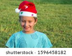 Small photo of Charming boy in a clownish cap of Santa Claus cheerfully smiles on a green lawn. Concept portrait and advertising photo