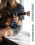 Small photo of The young woman in the striped t-shirt sitting on the windowsill and playing acoustic guitar. Close up of the hands with bracelets. Girl picks a chord