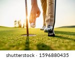 Small photo of lifestyle, golf, activity, outdoor, sport, golfer concept. Golfers collect golf balls that hole in the green grass on the golf course in the morning.