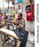 Small photo of Gurgaon, Haryana / India - December 22nd 2019 : A tailor in a market in Indian locality doing his daily job. These tailors usually work on adhoc basis without any contractual agreement with anyone.