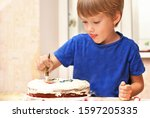 Small photo of Little kid boy decorating cake and smacks his lips. Cooking children at home kitchen, happy sweet childhood, people making tasty appetite food