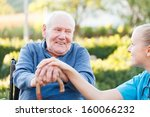 Small photo of Young happy doctor giving support to his elderly patient.