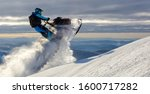 A Snowmobile Rider Jumps In A...