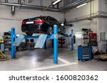 Small photo of Novosibirsk, Russia - 08.01.2018: Used car BMW stands on the stand wheel alignment convergence of the car in the workshop for repair of vehicles Auto service industry on blue lift