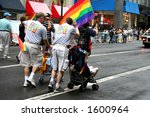 Gay couple with their adopted children marching on pride parade on fifth avenue in borough of Manhattan of city of New York - stock photo