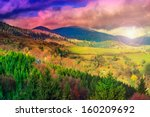 autumn landscape. forest on the hillside covered with red and yellow leaves. over the mountains the beam of light falls on a clearing at the top of the hill. - stock photo