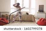 Young Woman Dancing With Vacuum ...