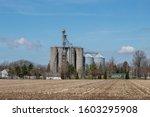 A Corn Field With Grain Silos...