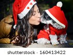 Stock photo beautiful woman hugging her dog with red christmas hat 160413422