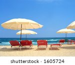 Exotic scene with parasols and red chairs near the ocean - stock photo