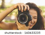 Beautiful brunette woman taking a picture in a park - stock photo