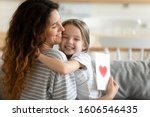 Small photo of Loving pre-school daughter preparing for mother surprise gave her handmade card with red heart symbol of love, 8 eight march spring holiday International Women or Mothers Day celebration event concept