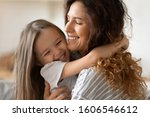 Small photo of Close up beautiful young mother snuggle little cheerful daughter laughing enjoy moment of tenderness having fun spend time together at home, next generation and offspring, unconditional love concept