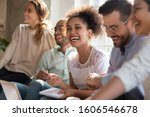 Small photo of Overjoyed multiracial young people sit in row have fun laughing studying together indoors, happy international diverse students joke chat brainstorm preparing for test making notes learning