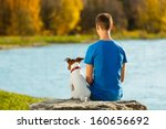 Stock photo boy and his dog sitting together enjoying the view 160656692