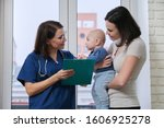 Doctor pediatrician talking with young mother holding her baby in her arms. Children medical care, health, help - stock photo