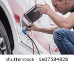 Caucasian RV Caravaning Technician Checking on Electric Hookup Outlet In Modern Travel Trailer. - stock photo