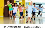 Small photo of Group of glad cheerful positive children practicing vigorous jive movements in dance class with female coach