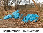 Small photo of Garbage, rubbish waste dumped in the environment. Wild landfill. Illegal dumping. The unauthorized, open dump of garbage among shrubs, thickets, leaves, trees by the fence next to the city path.