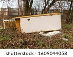 Small photo of Garbage, rubbish waste dumped in the environment. Wild landfill. Illegal dumping. The unauthorized, open dump of garbage. An old, broken fridge among bushes, trees by a concrete fence in the city.