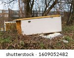 Small photo of Garbage, rubbish waste dumped in the environment. Wild landfill. Illegal dumping. The unauthorized, open dump of garbage. An old, broken fridge among shrubs, thickets by a concrete fence in the city.