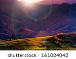 autumn landscape. forest on a hillside covered with red and yellow leaves. over the mountains in evening - stock photo